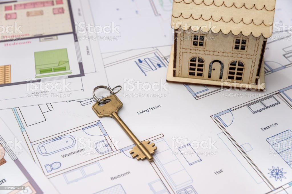 Wooden house model with key on house plan