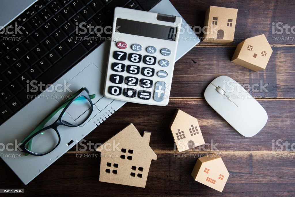 Wooden house, paper house, calculator, glasses and Laptop note book on wooden table background with copy space.Real estate concept, New house concept, Finance loan business concept – Foto