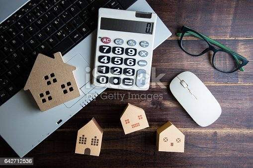 Wooden house, paper house, calculator, glasses and Laptop note book on wooden table background with copy space.Real estate concept, New house concept, Finance loan business concept