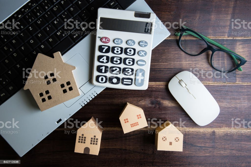 Wooden house, paper house, calculator, glasses and Laptop note book on wooden table background with copy space.Real estate concept, New house concept, Finance loan business concept stock photo