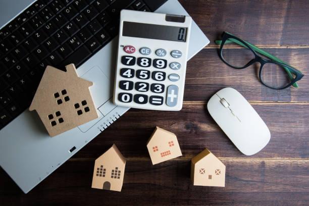 Holzhaus, Papierhaus, Taschenrechner, Gläser und Notebook Notizbuch auf Holztisch Hintergrund mit Textfreiraum. Immobilien-Konzept, neues Haus-Konzept, Finanzierung-Darlehen-Business-Konzept – Foto