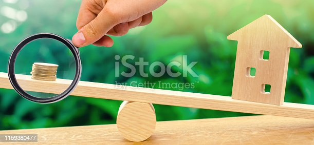istock Wooden house with coins on the scales. The concept of real estate purchase. Sale of property. Payment of the mortgage. Redemption of taxes. Tax refund. Credit for the apartment. 1159380477