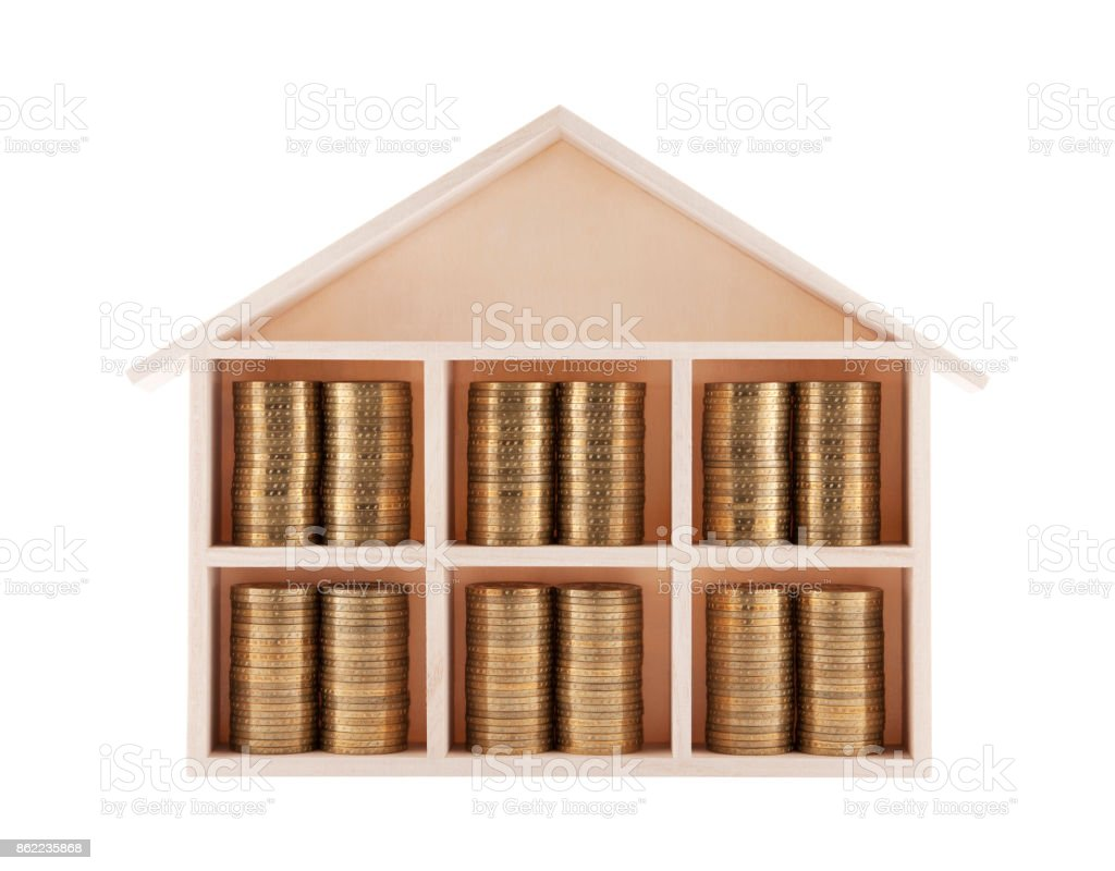 Wooden house with coins stock photo