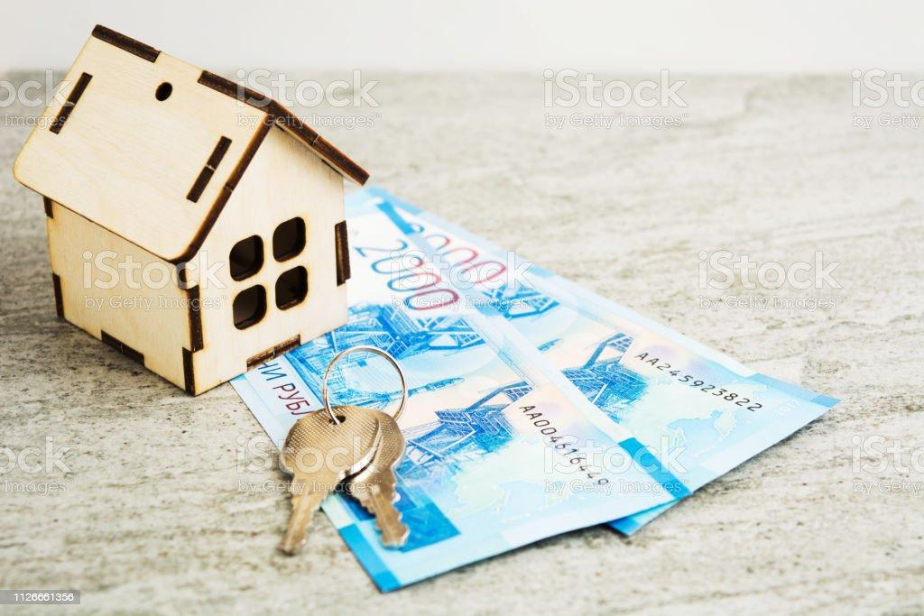 Casa de madeira com chaves e rublos em backgorund cinza, comprar o conceito de casa - foto de acervo