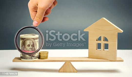 istock Wooden house with money on the scales. The concept of real estate purchase. Sale of property. Payment of the mortgage. Redemption of taxes. Tax refund. Credit for the apartment. 1148795529