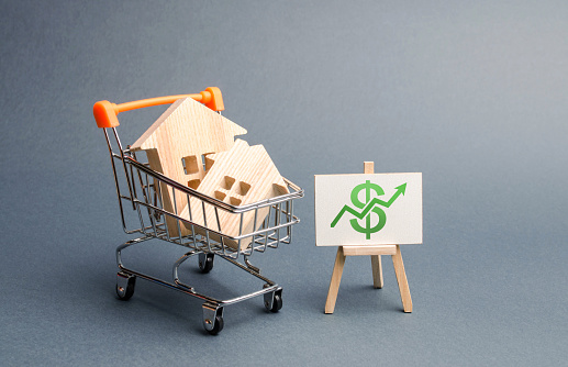 831745600 istock photo Wooden houses in a trading cart and green arrow up. Increasing the cost and liquidity of real estate. Attractive investing. rising prices or renting. The boom in the property market, excitement, hype 1157940660