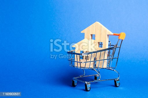 istock Wooden houses in a trading cart. The concept of buying a house or apartment. Affordable housing. Profitable and cheap loans for real estate. Buying a home. Mortgage and loan. Place for text 1163900531