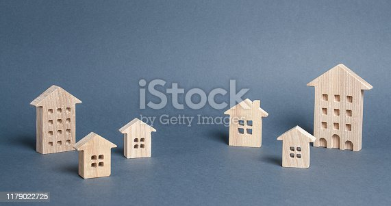 istock Wooden houses on a gray background. City, settlement. Buying a home. Real estate market. The concept of travel and choosing a new place of residence. Moving to another house. Search for options 1179022725