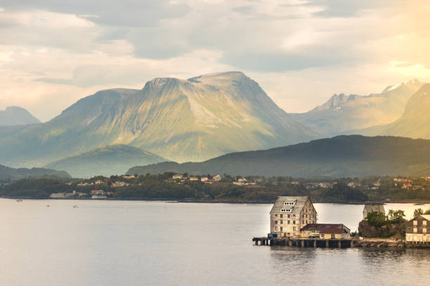 Wooden houses placed on a wooden dock with large mountains in the background in Alesund, Norway. stock photo
