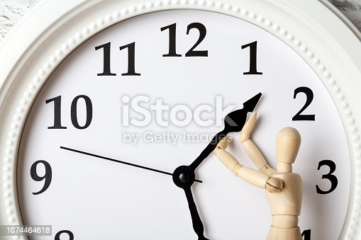istock Wooden human figure trying to stop the arrow of the clock. Deadline concept 1074464618