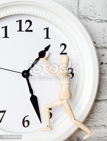 istock Wooden human figure trying to stop the arrow of the clock. Deadline concept 1075402676