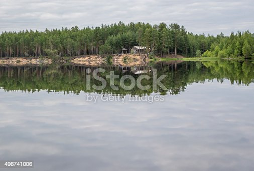 Wooden hut in forest, on the island for hunters and fishermen in Paanajärvi National Park, Karelia, Russia. Summer water landscape. Thousand Lakes Region