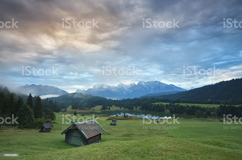 wooden hut o meadow by Geroldsee lake at sunrise stock photo