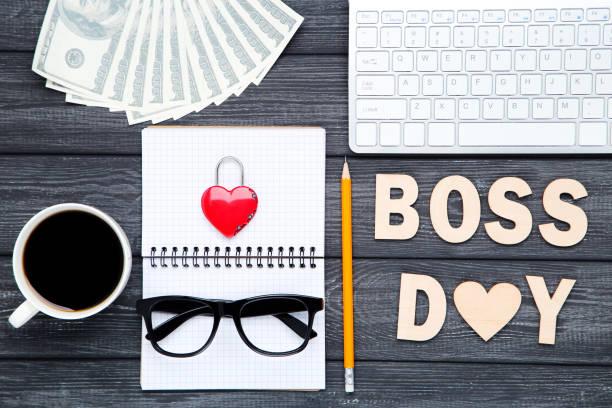 inscripción de madera boss day con taza de café, teclado y billetes en dólares sobre fondo de madera negro - boss's day fotografías e imágenes de stock