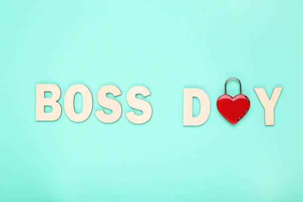 inscripción de madera boss day con candado en forma de corazón sobre fondo azul - boss's day fotografías e imágenes de stock