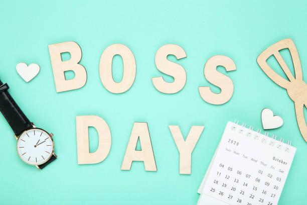inscripción de madera boss day con reloj de pulsera, pajarita y calendario de papel sobre fondo azul - boss's day fotografías e imágenes de stock