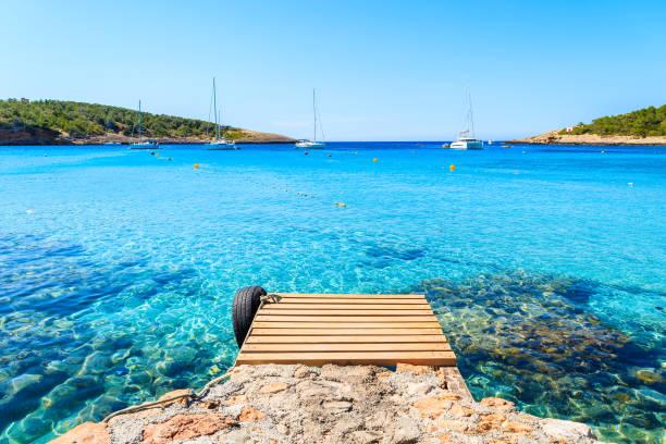 wooden jetty and view of azure blue sea with sailing boats in distance, cala portinatx bay, ibiza island, spain - ibiza imagens e fotografias de stock