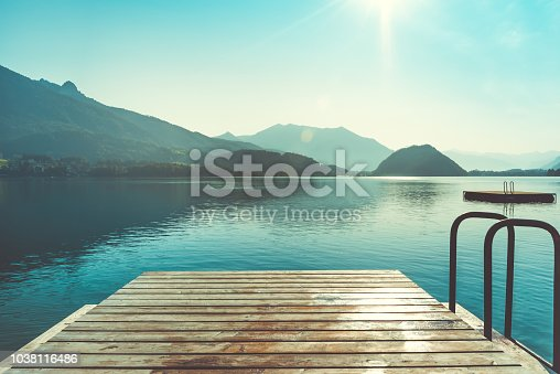 Wooden jetty for swimming in mountain lake in Austria. Swimming at early morning. European resort in mountains