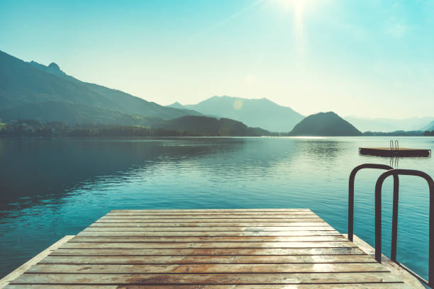Wooden jetty for swimming Wooden jetty for swimming in mountain lake in Austria. Swimming at early morning. European resort in mountains lake stock pictures, royalty-free photos & images