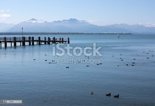 Wooden jetty leading into lake Chiemsee with the German Alps in the background