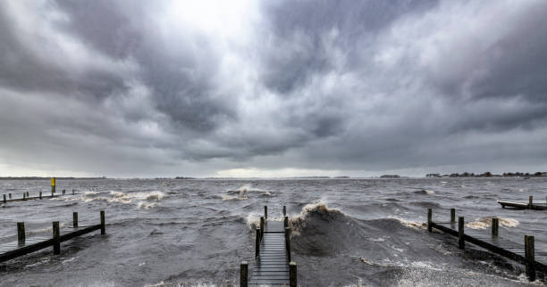 Wooden jetty on the shore of a lake with an approaching thunderstorm stock photo