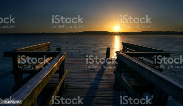 Photo of Wooden jetty with benches on a frozen lake in the light of the golden rising sun, beautiful landscape scenery, concept for a new beginning every day, copy space