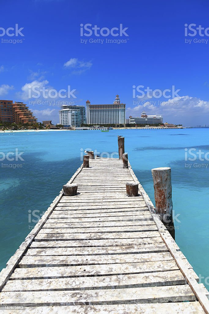 Wooden jetty with row of tourist resorts in background stock photo