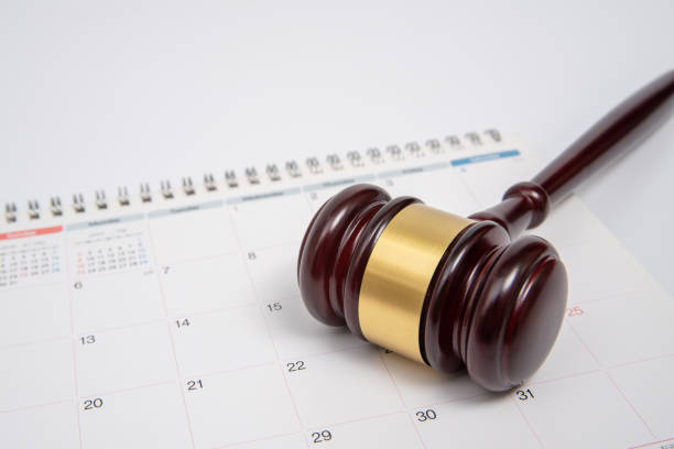 A wooden judge gavel and calendar isolated on white background. stock photo