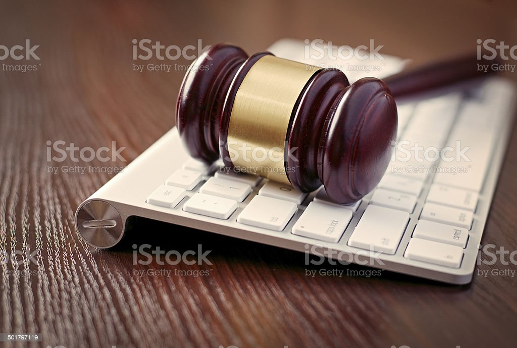Wooden judges gavel on a computer keyboard stock photo