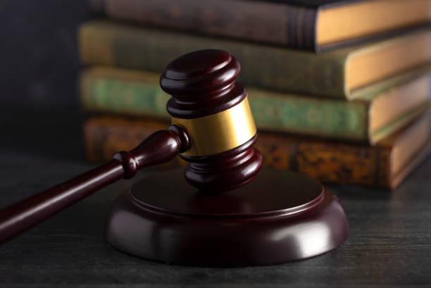 houten rechters gaf op een bureau met boeken op de achtergrond - exploitatie stockfoto's en -beelden