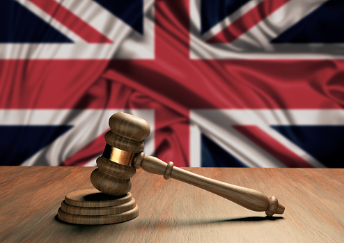 Wooden judge's gavel Symbol of law and justice with the flag of England. English Supreme Court. 3D Rendering