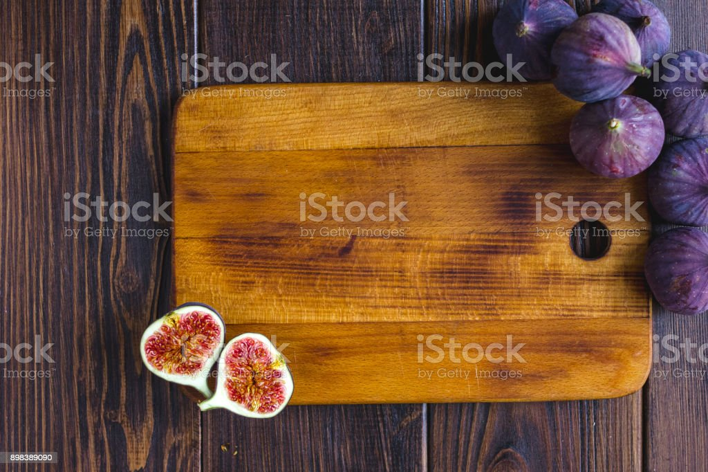 Wooden kitchen board with fig fruits on it. stock photo