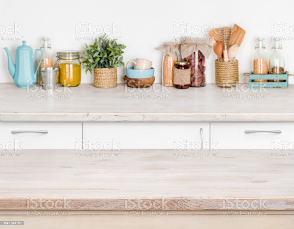 Wooden kitchen table over blurred furniture shelf with food ingredients stock photo