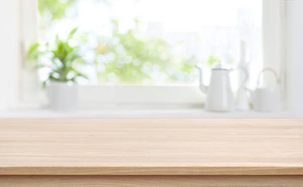 Wooden kitchen table with background of window for product display stock photo