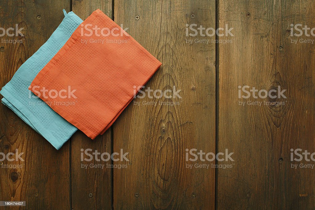 Wooden kitchen table with two folded dishcloths on stock photo