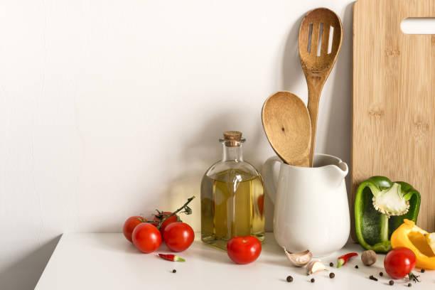 houten keukengerei, olijfolie en groenten op tafel wand achtergrond. sjabloon voor tekst - oil kitchen stockfoto's en -beelden