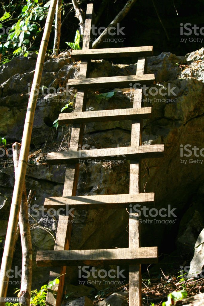 wooden ladder against a stone of the mountain stock photo