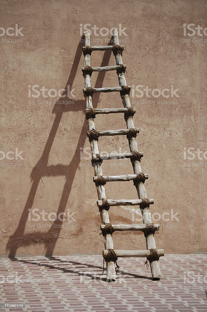 Wooden ladder on Adobe wall and shadow royalty-free stock photo