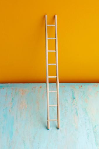 Wooden ladder on color background