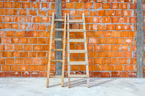 Front view on used wooden ladders, leaning against the wall for access, reaching to higher place at construction site.