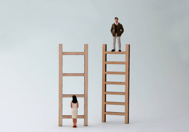 Wooden ladders and miniature people. The concept of gender inequality in promotion. Wooden ladders and miniature people. The concept of gender inequality in promotion. discriminatory stock pictures, royalty-free photos & images