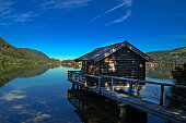 Wooden Lake house with relection green trees and blue clear sky. Tegernsee, Munich, Germany