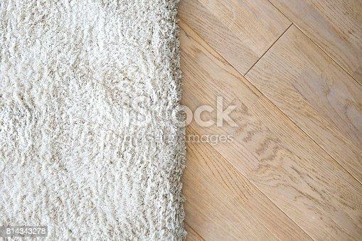 istock Wooden laminate floor and soft carpet 814343278