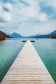 Scenic panorama view of an idyllic wooden landing stage on a beautiful lake in the Alps on a moody cloudy day in summer with retro vintage filter effect