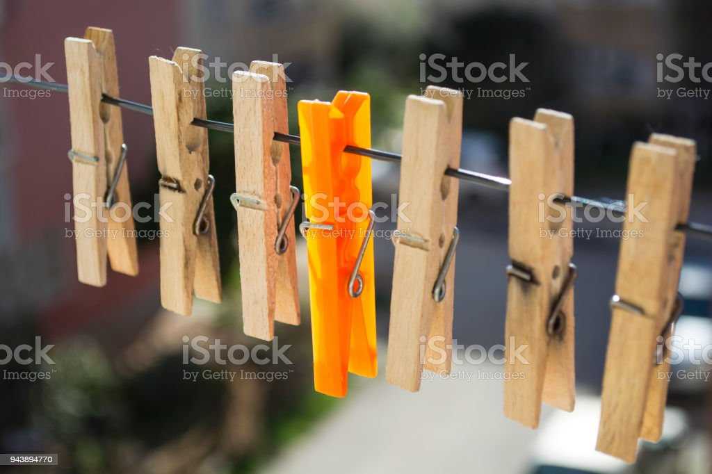 wooden laundry latches on a rope and an orange laundry latch between the latches stock photo