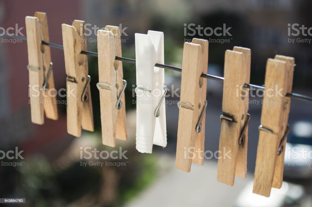wooden laundry latches on a rope and an white laundry latch between the latches stock photo