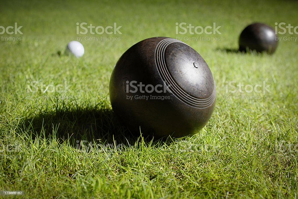 Wooden lawn bowls on a bowling green around jack stock photo