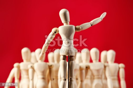 A little wooden figurine with its arm raised addresses an out-of-focus audience of other wooden puppets at a rally, meeting, seminar or social occasion, or he could be a choir master leading them in a choral performace.  Red background with some copy space.