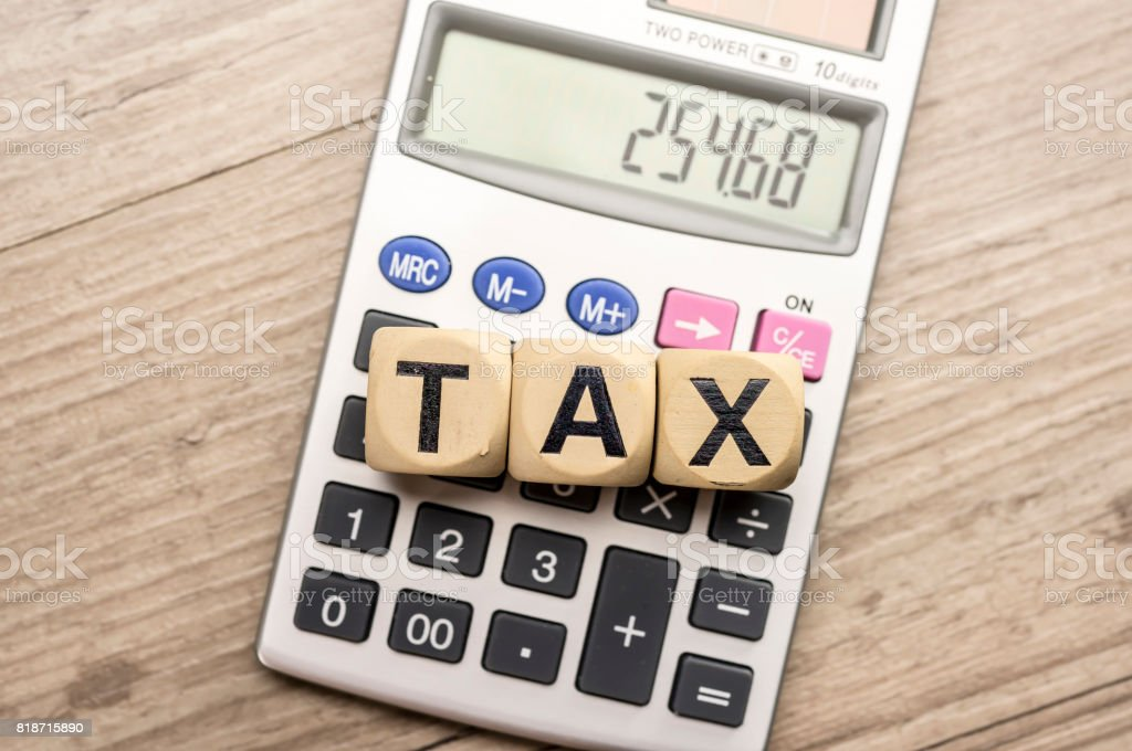 Wooden letter block assemble the word tax and calculator stock photo