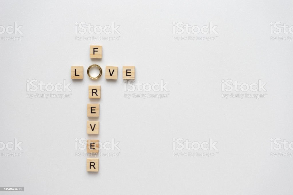 Wooden letters and wedding ring speling love for ever. Top view. royalty-free stock photo